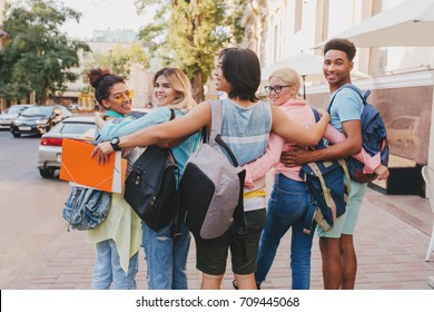 Outdoor portrait from back of international students hanging out carrying backpacks with books. Handsome black boy looking over shoulder while his long-haired friend embracing girls.