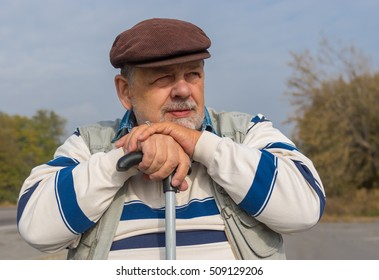 Outdoor portrait of bearded senior man with walking stick