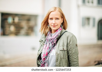 Outdoor portrait of beautiful blond woman, posing outdoors, wearing khaki color parka and pink scarf