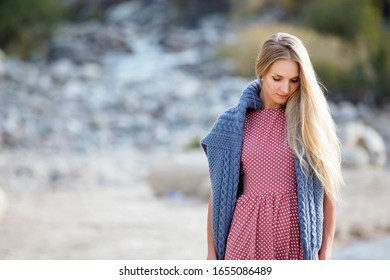 Outdoor portrait of a beautiful blonde woman wearing pink dress and blue knitted sweater by the river