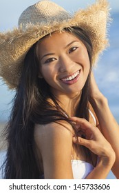 Outdoor portrait of a beautiful Chinese Asian young woman or girl wearing a white bikini and straw cowboy hat at a beach