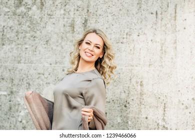 Outdoor portrait of beautiful elegant woman wearing silk dress