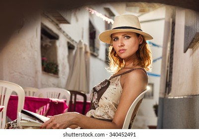 Outdoor portrait of a beautiful female tourist visiting old town in Moraira, Spain. Middle aged woman looking towards the camera.