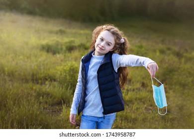 Außenporträt eines schönen Mädchens, das eine chirurgische Maske in der Hand hält und endlich atmen kann
