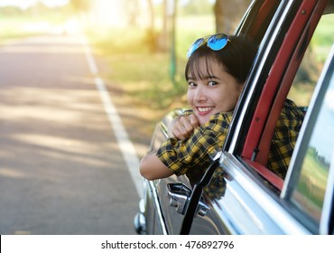 Outdoor portrait of beautiful girl on car holidays.Smiling young pretty woman in the car