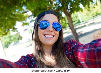 Outdoor portrait of beautiful girl taking a selfie with mobile phone in city.