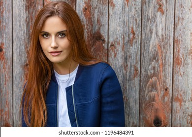 Outdoor portrait of beautiful girl or young woman with red hair wearing a ble jacket and white t-shirt leaning against an old wooden building