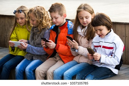 Outdoor portrait of beautiful girls and boys playing with phones