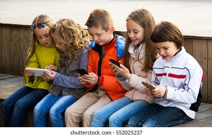 Outdoor portrait of beautiful girls and boys playing with smartphones and smiling