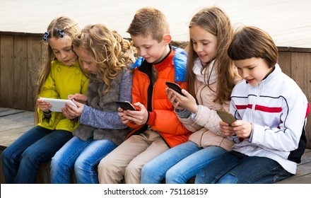 Outdoor portrait of beautiful girls and boys playing with phones and smiling