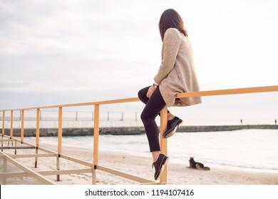 Outdoor portrait beautiful happy brunette woman sitting on the railing, stylish wear, skin care, brunette hipster enjoy the sea, happy model, dreamer, girl in white shirt, laugh, bohemian woman rest