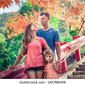 Outdoor portrait of a beautiful happy family. Father, mother and daughter together