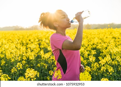 Outdoor portrait of beautiful happy mixed race African American girl teenager female young woman athlete runner drinking water from a bottle field of yellow flowers at sunset in golden evening sunshin