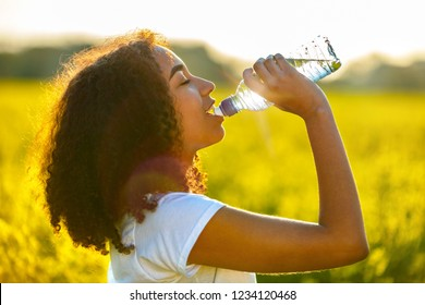 Outdoor portrait of beautiful happy mixed race African American girl teenager female young woman drinking water from a bottle in a field of yellow flowers at sunset in golden evening sunshine