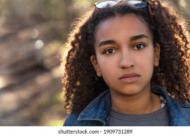 Outdoor portrait of beautiful happy mixed race African American girl teenager female child looking thoughtful or sad