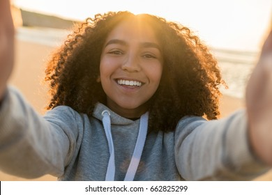 Outdoor portrait beautiful happy mixed race African American girl teenager female young woman on a beach taking selfie photograph smiling laughing with perfect teeth in golden sunset evening sunshine