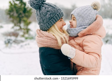 Outdoor portrait of beautiful happy woman holding her toddler girl, smiling and laughing together during walking in the park on snowing day. Christmas mood. Family portrait. Motherhood and childhood