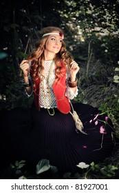 outdoor portrait of beautiful hippie girl sitting in woods