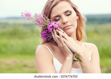 outdoor portrait of a beautiful middle aged blonde woman in a field with flowers