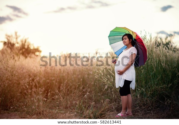 Outdoor portrait of beautiful pregnant woman in relaxing in the summer nature meadow. maternity and new family concept with umbrella colorful