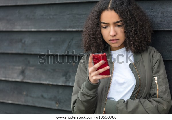 Outdoor portrait of beautiful sad depressed mixed race African American girl teenager female young woman texting or using social media on red cell phone wearing green bomber jacket