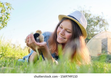 Outdoor portrait of beautiful smiling teenage girl on farm with two newborn chicks in hand, nature background green grass sky