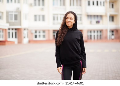 Outdoor portrait of a beautiful sporty woman in black hoody