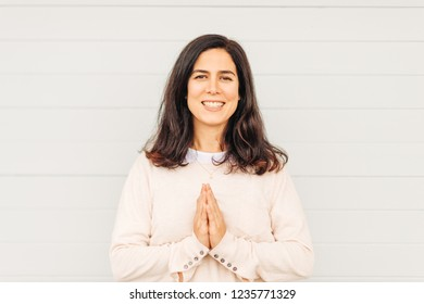 Outdoor portrait of beautiful woman with dark hair, holding hands next to chest, namaste gesture sign