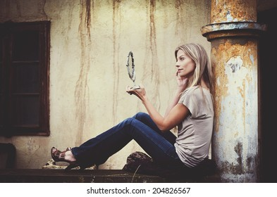 Outdoor portrait of beautiful woman posing by the old house