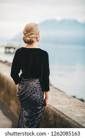 Outdoor portrait of beautiful woman wearing black velvet and sequin dress, posing next to lake, back view
