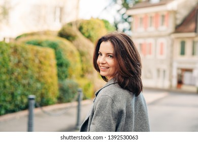 Outdoor portrait of beautiful woman wearing grey coat, smiling, looking back over the shoulder
