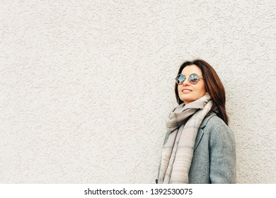 Outdoor portrait of beautiful woman wearing grey coat, warm scarf and sunglasses with blue sky clouds reflection