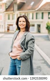 Outdoor portrait of beautiful woman wearing grey coat