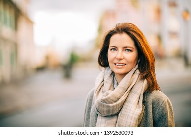 Outdoor portrait of beautiful woman wearing grey coat