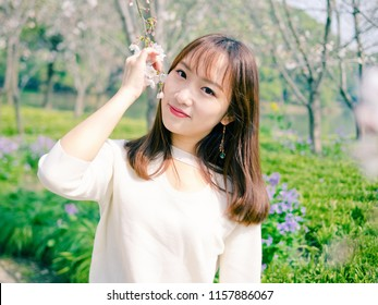 Outdoor portrait of beautiful young Chinese girl smiling among blossom cherry tree brunch in spring garden, beauty, summer, emotion, expression and people concept.