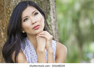 Outdoor portrait of a beautiful young Chinese Asian young woman or girl with natural green background