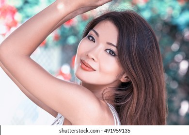 Outdoor portrait of a beautiful young female Chinese Asian young woman or girl