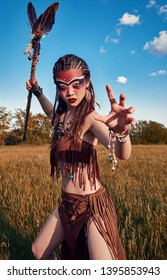 Outdoor portrait of the beautiful young shamaness (witch doctor) in field at sunset. Lovely shaman (enchantress) preparing for fight