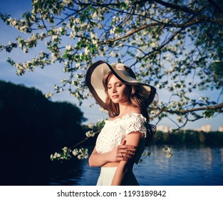 Outdoor portrait of beautiful young woman wearing  hat posing in the blooming garden. Female spring fashion concept