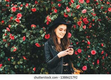 Outdoor portrait of beautiful young woman wearing black leather jacket and hat, posing in camelia flowers, holding smartphone