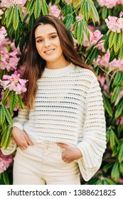 Outdoor portrait of beautiful young woman white knitted pullover, posing in spring garden