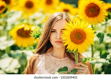 Outdoor portrait of beautiful young woman with sunflowers, health and lifestyle, girl hiding behind flowers
