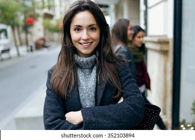 Outdoor portrait of beautiful young woman looking at camera.