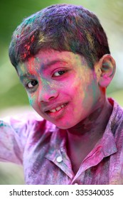 Outdoor portrait of boy with different colors on his face celebrates the Indian festival Holi