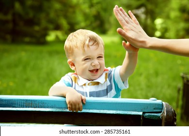 outdoor portrait of a boy on green background. happy child on walk in the summer park. Give five gesture support. high five