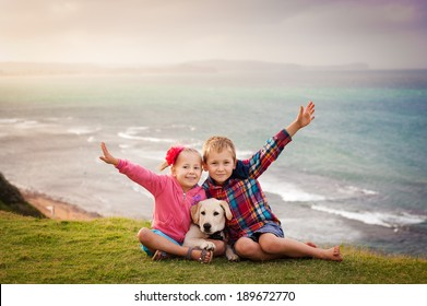Outdoor portrait of brother and sister having fun with their pet dog labrador with ocean view