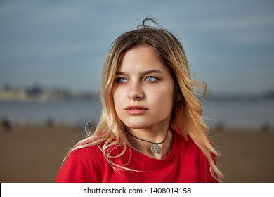 Outdoor portrait of caucasian ethnicity white young adult woman 20-24 years old in red T-shirt with blond hair, she is looking thoughtfully into the distance.