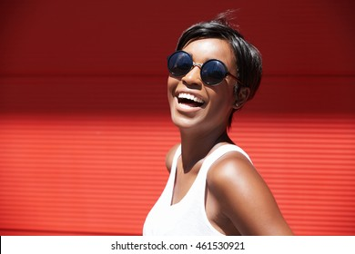Outdoor portrait of chic African American model in hipster sunglasses posing with happy and cheerful face expression, laughing black female looking excited and carefree, feeling good and enjoying life
