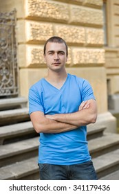 Outdoor portrait of a confident man in jeans and blue t-shirt, in front of a stone wall