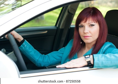 Outdoor portrait of a confident young caucasian woman sitting in her new car and looking at camera
